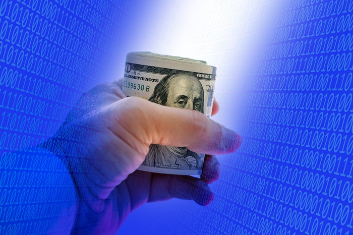 Hand holding roll of $100 bills with a matrix of 1's and 0's on a blue background