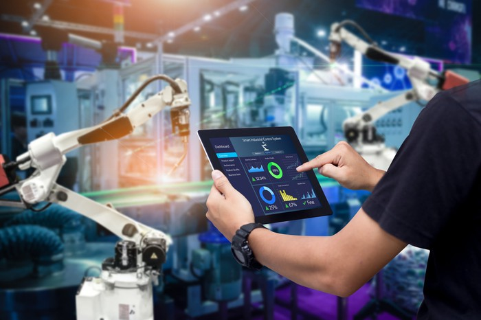 Person in factory controlling robotic arm with tablet