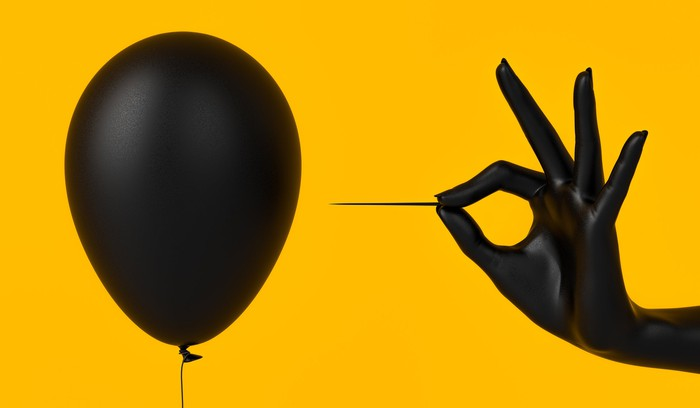 Hand holding pin next to balloon