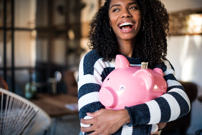 A woman hugs a piggy bank with money tucked in the slot.