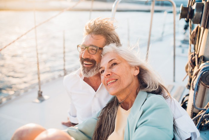 Older couple sitting on a boat smiling