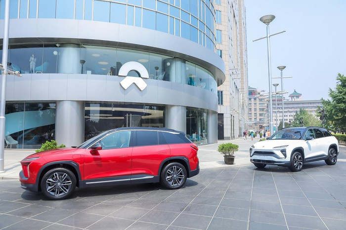 Two NIO electric SUVs are shown parked in front of a company facility.