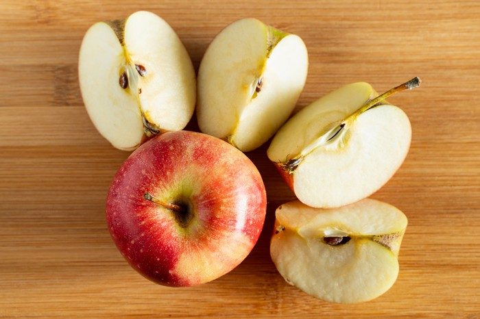 One whole apple is next to another apple that's cut into four slices.
