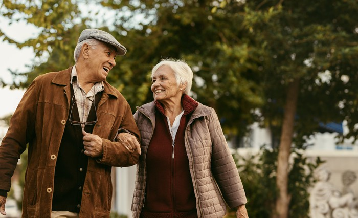 Smiling older man and woman linking arms and walking outdoors