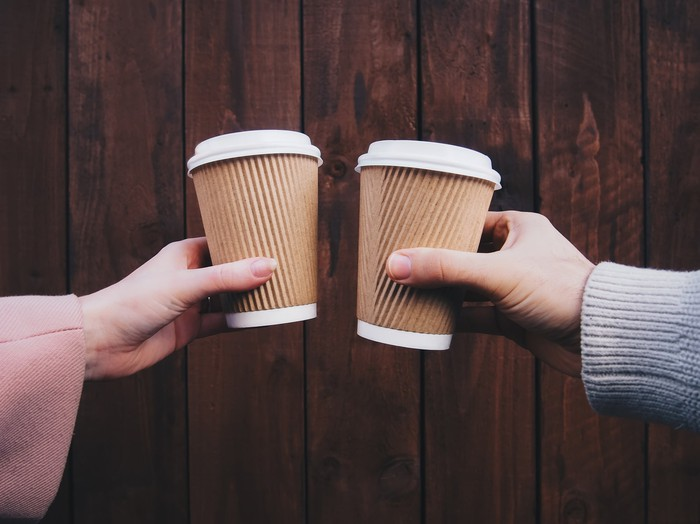 Two cups of coffee are juxtaposed against a wood panel background.