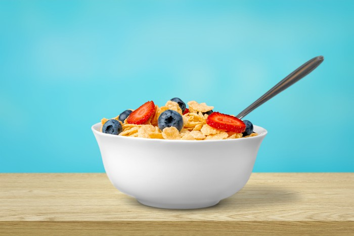 A bowl of cereal with fruit in it sitting on a table against a blue background.