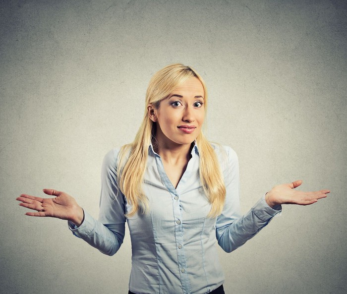 A confused woman shrugs her shoulders.