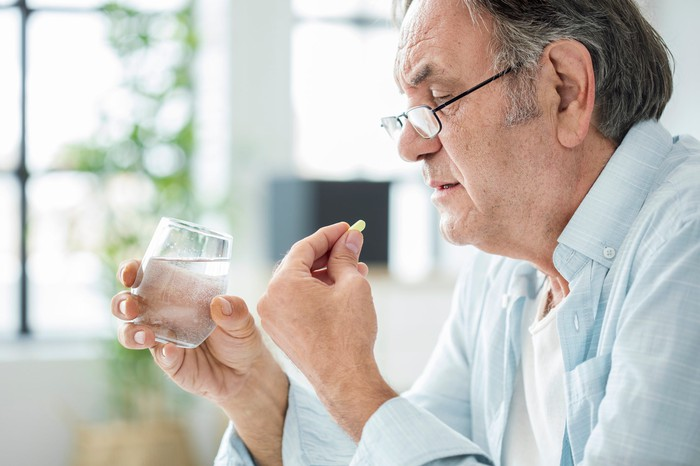 An older man holds a pill in one hand and a glass of water in the other.