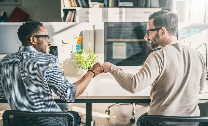 Two business partners sitting at desk celebrating success with a fist bump