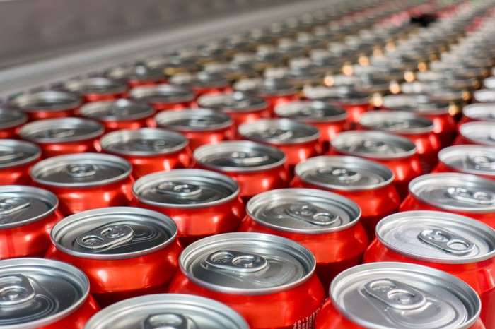 Rows of red aluminum soda cans seen from overhead in a manufacturing facility.