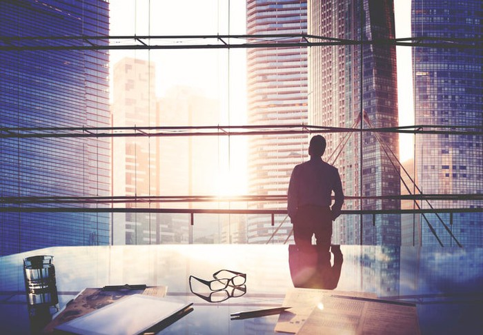 A silhouette of a businessman in front of a city skyline.