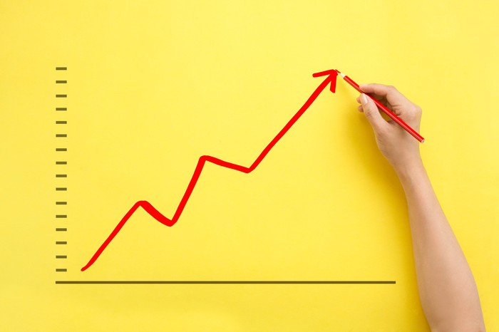 A person's hand uses a red pencil to show a stock price rising on a chart.