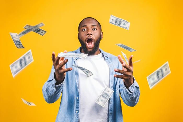 A man smiling as $100 bills swirl around him.