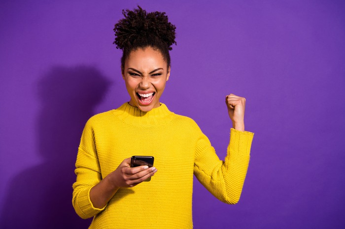 An extremely happy person in a yellow sweater holds a smartphone.