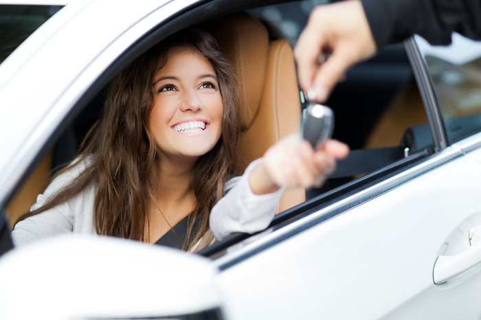 A young woman sitting in her car she just bought is handed the keys.