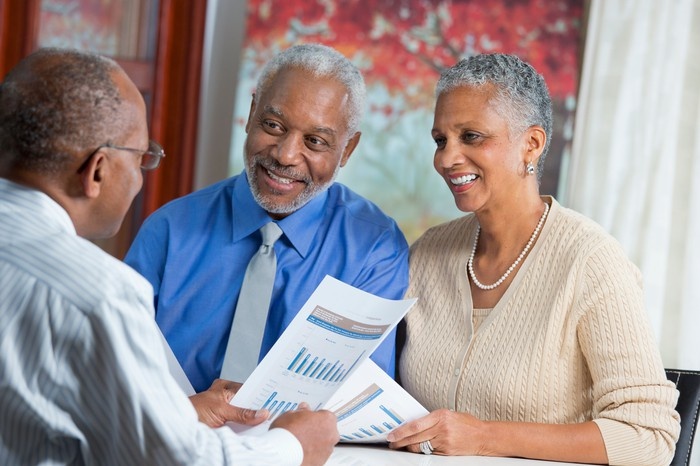 Three adults reviewing financial paperwork.