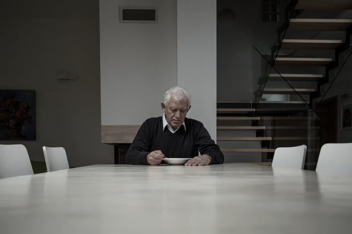 Sad older man sitting alone at table.