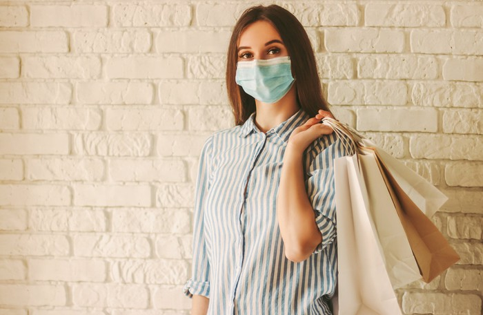 A woman, wearing a mask, holds shopping bags as she stands in front of a brick wall.