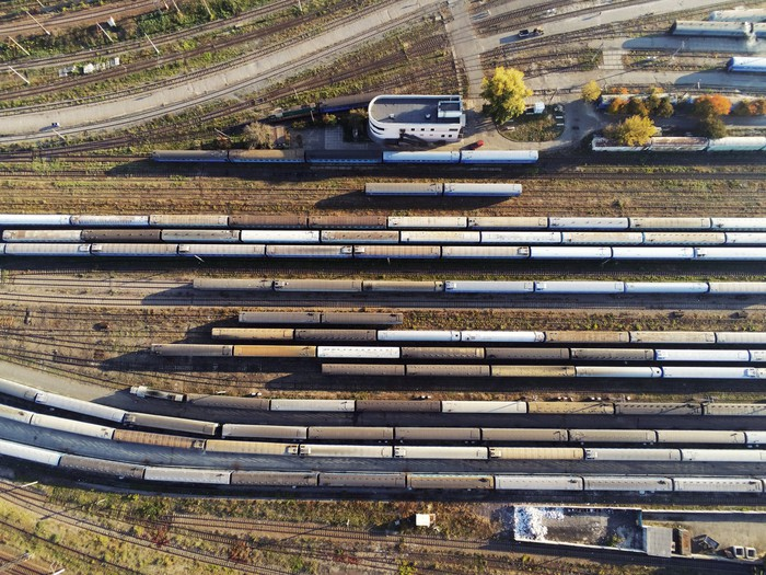 A freight train yard with many trains waiting on tracks