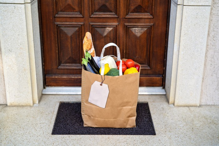bag of groceries sitting on doormat from delivery service