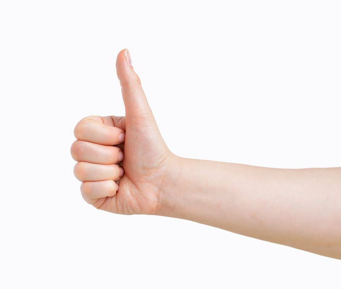 A hand points its thumb up against a white background.