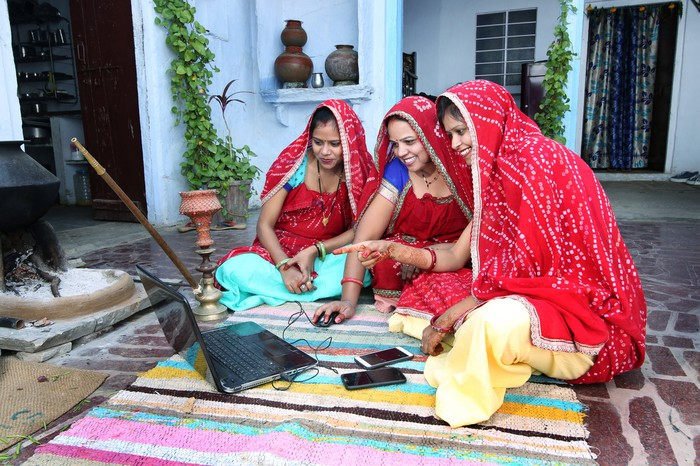 Traditional Indian women with smartphones and a laptop.