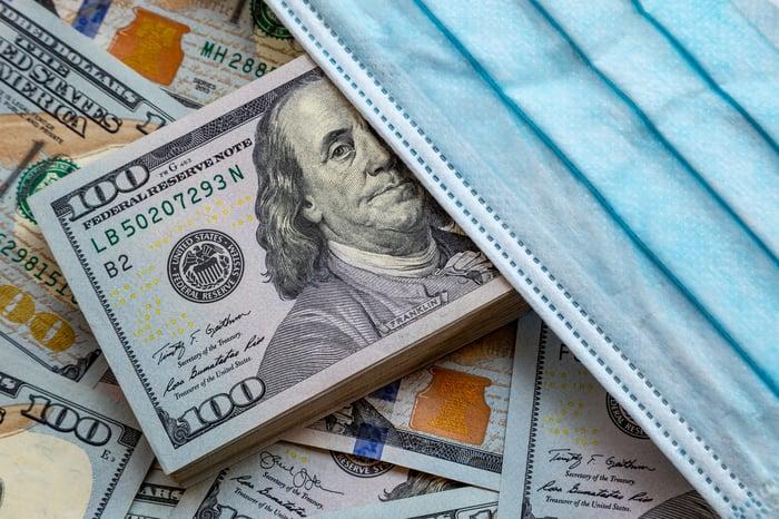 A pile of hundred-dollar bills under a surgical mask.