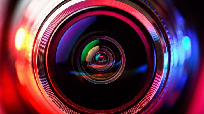 Close-up of camera lens, with red and blue light on either side.