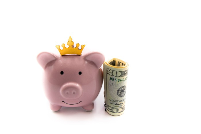 Piggy bank with a crown on top of it next to a roll of $20 bills