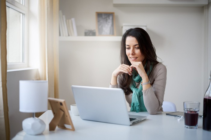 A person sitting at laptop at home.