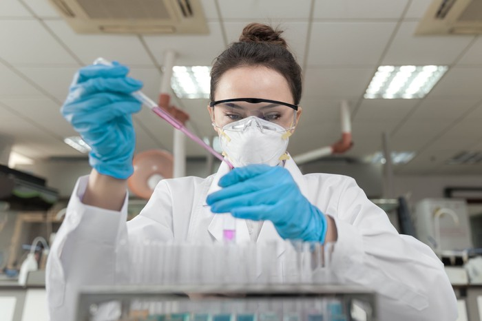 A lab technician with a pipette and pink liquid.