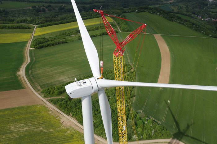 Crane installing blades on wind turbine.