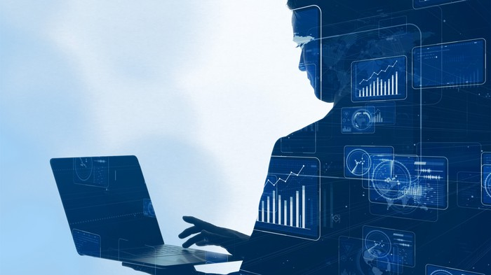 Silhouette of a man holding a laptop and typing with the other hand, with various charts and graphs superimposed over the figure