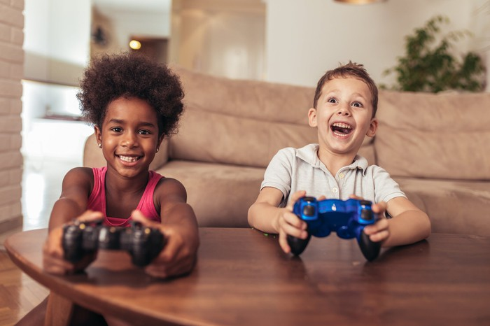 Two kids sitting in between a coffee table and a couch holding video game controllers and smiling