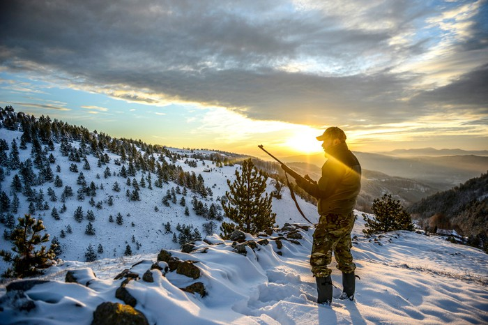 A man dressed for the outdoors holding a rifle on a snowy mountainside