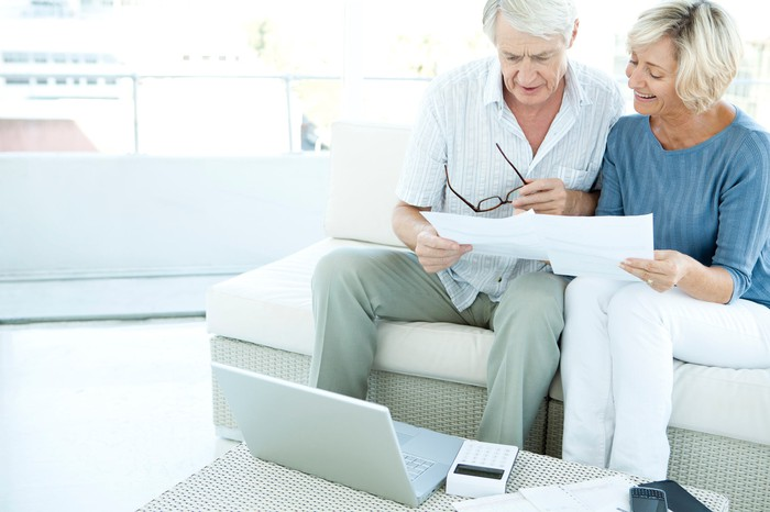 Older couple looking at documents in front of a laptop and a calculator.
