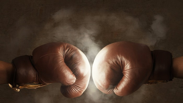 Two boxing gloves are hitting each other.