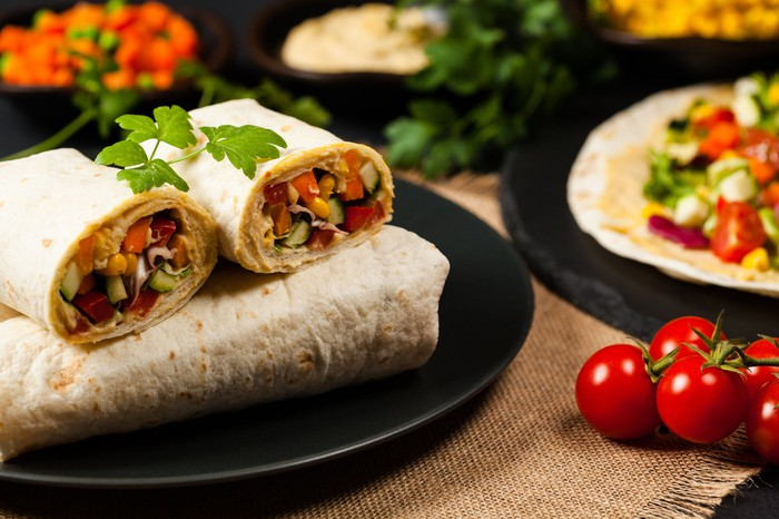 Burritos on a plate, next to tomatoes and other fixings.