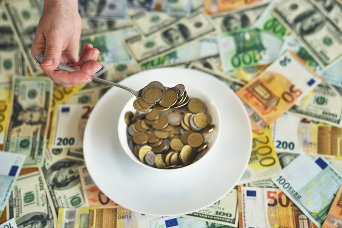 Coins in bowl being scooped out by spoon with various currency underneath