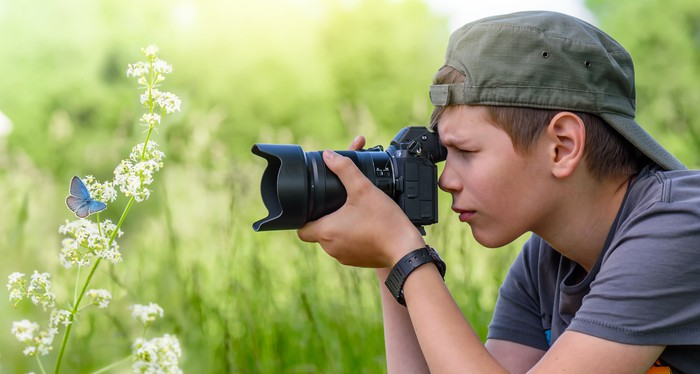 Boy taking a picture of butterfly with digital camera.
