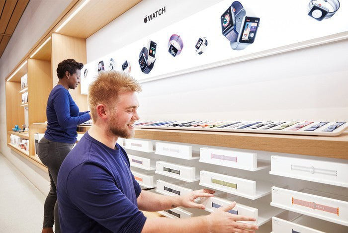 Apple store employees straightening Apple Watch bands on display.