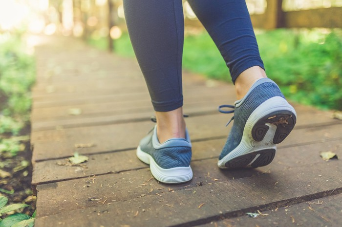 Blue running shoes being worn on wooden walkway