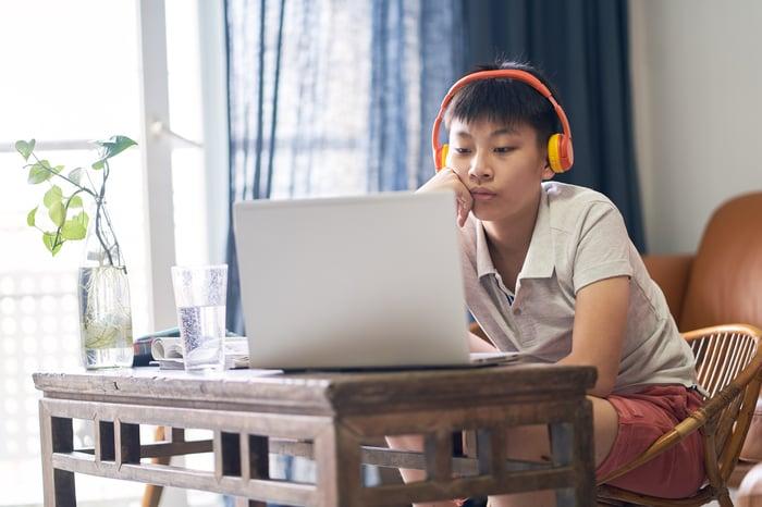 Teen with headphones looking at laptop
