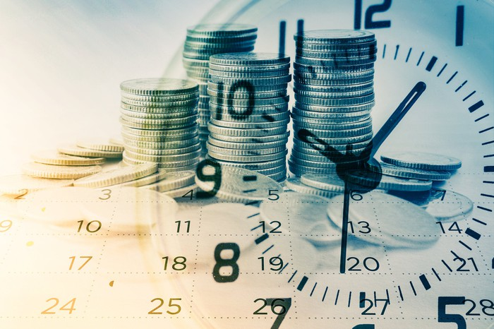 A clock in front of a pile of cash.