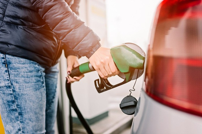 Person filling up car at gas station.