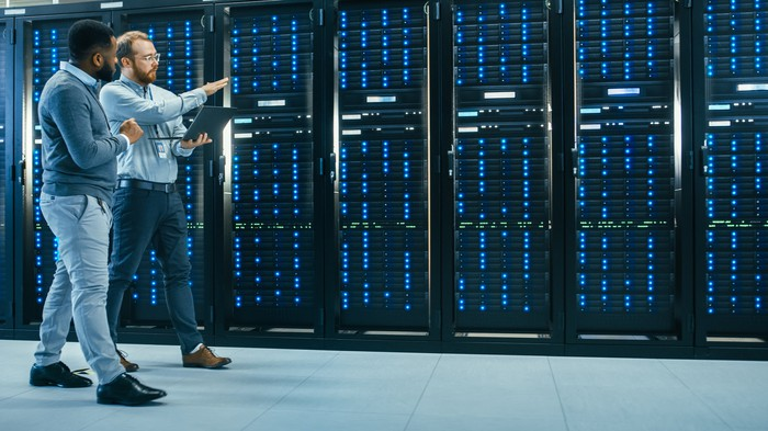 Two men walking past a row of servers.