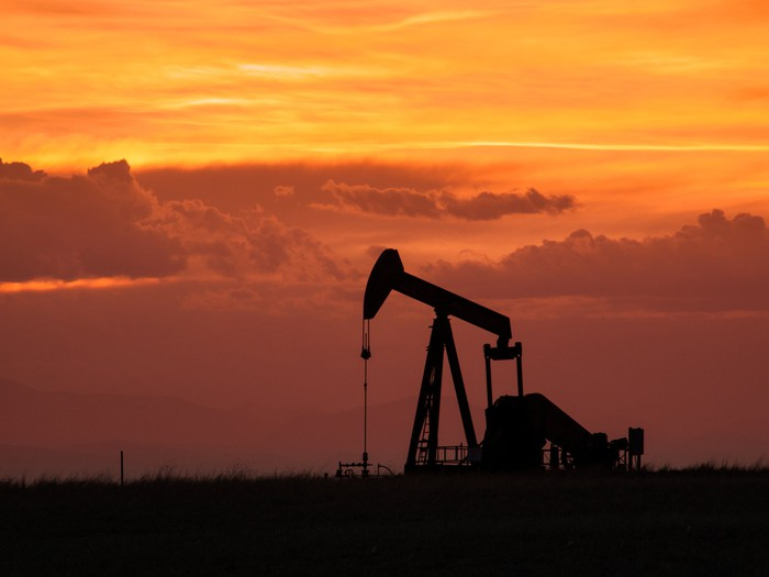 An oil pump jack with an orange sky in the background.