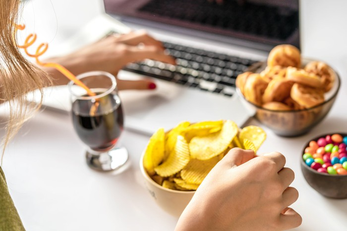 Woman eating a snack while at her computer.