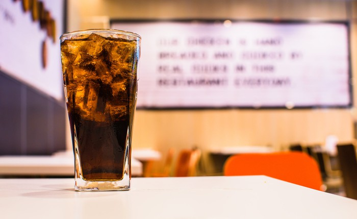 A glass of cola on a diner table.