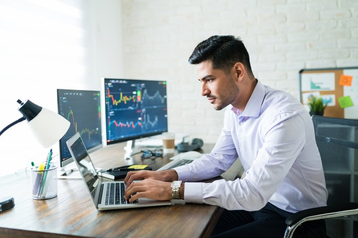An investor works on his laptop with stock performance screens in the background.